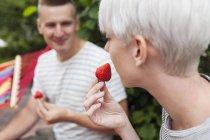 Couple eating strawberries in garden — Stock Photo