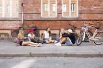 Ragazze adolescenti e ragazzi adolescenti (14-15) seduti sul marciapiede — Foto stock
