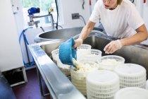 Frau Vorbereitung Hüttenkäse in Großküchen — Stockfoto