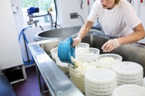 Woman preparing cottage cheese in commercial kitchen — Stock Photo