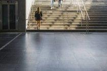 Femme qui marche escalier d'en bas — Photo de stock