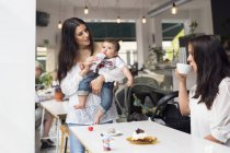 Mother holding baby son (6-11 months) and talking with friend in cafe — Stock Photo
