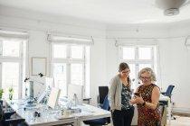 Compañeros de trabajo en teléfono móvil en la oficina - foto de stock