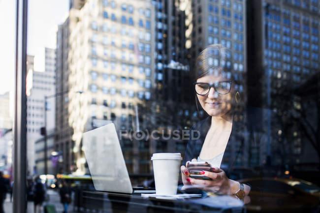 Empresária com tecnologias no café — Fotografia de Stock