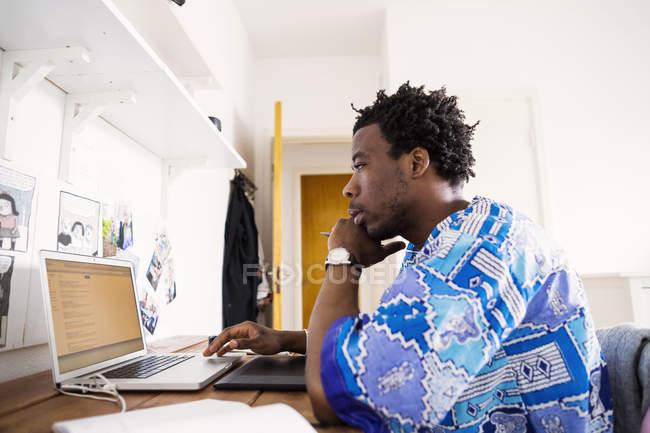 Hombre usando la computadora portátil en casa - foto de stock