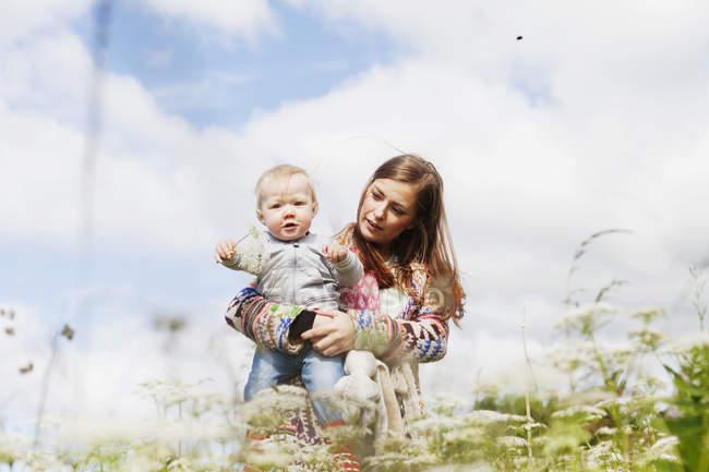 Hijo con madre en la playa contra - foto de stock