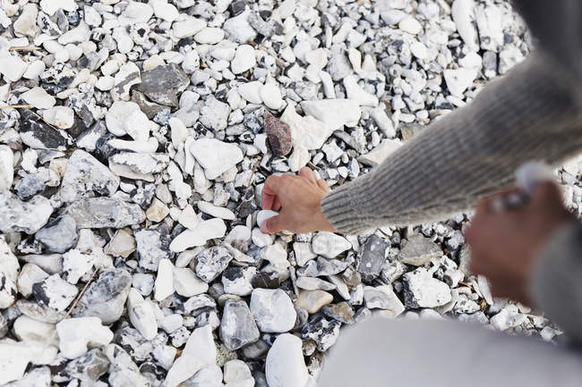 Man picking stones at beach — Stock Photo
