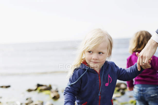 Daughters with father at beach — Stock Photo