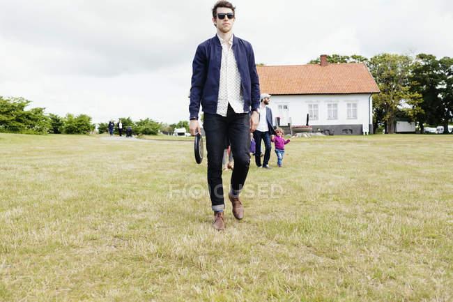 Família andando no campo gramado — Fotografia de Stock