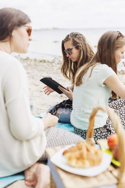 Women sitting at beach — Stock Photo