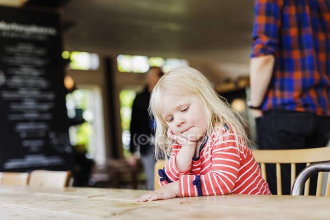 Menina olhando para baixo, enquanto está sentado — Fotografia de Stock