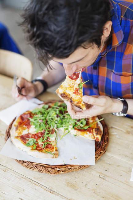 Hombre comiendo pizza en el restaurante - foto de stock
