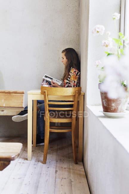 Frau Lesebuch im café — Stockfoto