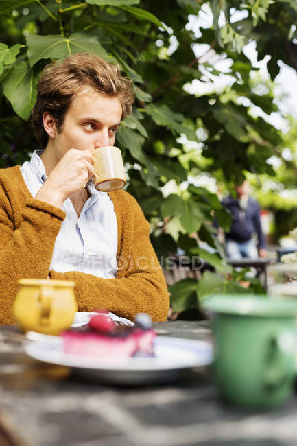 Man drinking coffee with cake — Stock Photo