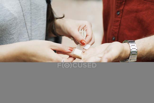 Mulher amarrando bandagem na mão masculina — Fotografia de Stock