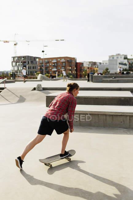 Femme faisant des skate trick dans le parc — Photo de stock