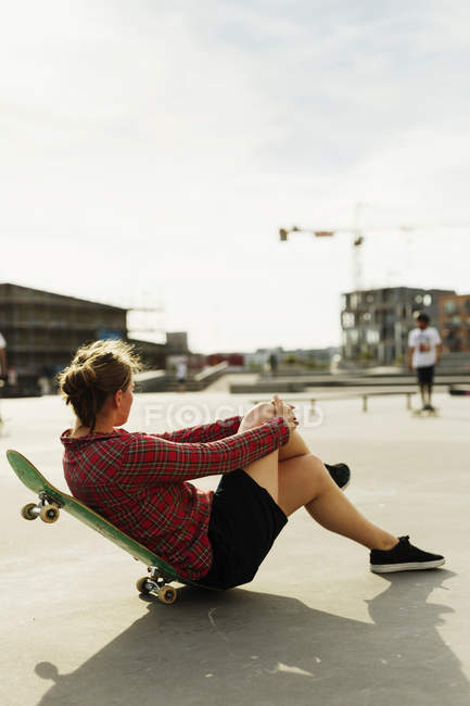 Woman leaning on skateboard at park — Stock Photo