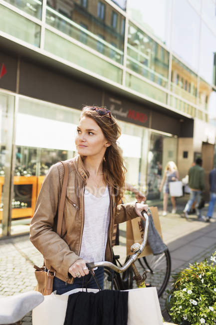 Woman with shopping bags and bicycle — Stock Photo