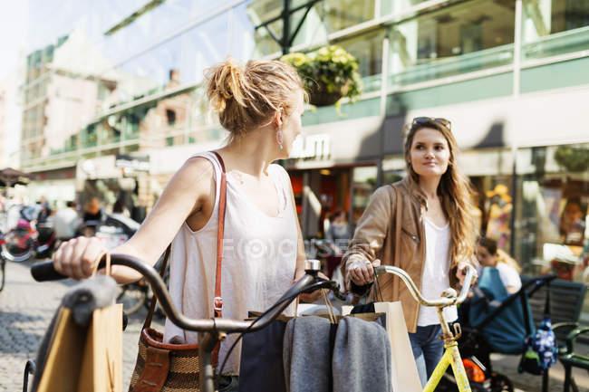 Жінки з велосипеди й сумки для покупок — стокове фото