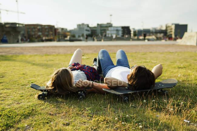 Teenage friends relaxing on skateboards — Stock Photo