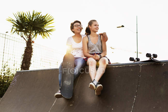 Friends sitting at edge of skateboard ramp — Stock Photo