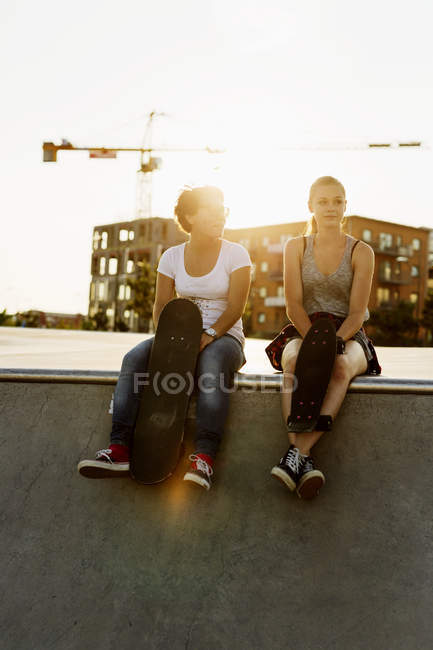 Friends sitting at edge of skateboard ramp — Stock Photo