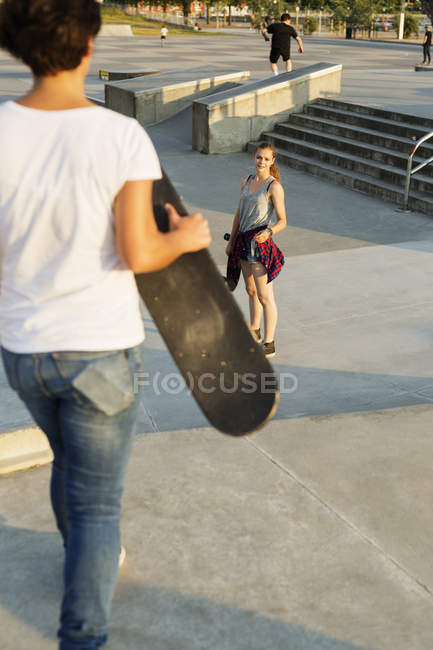 Girl looking at female friend in skate park — Stock Photo