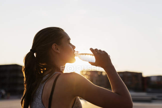 Женщина пьет воду в скейт-парке — стоковое фото
