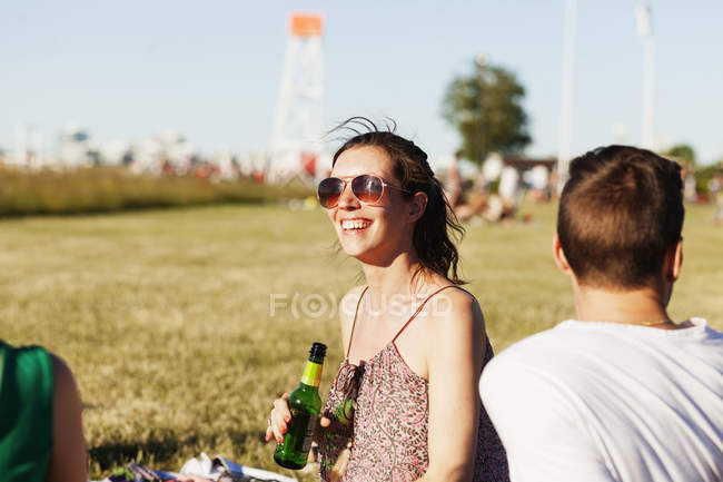 Woman holding beer bottle at picnic — Stock Photo
