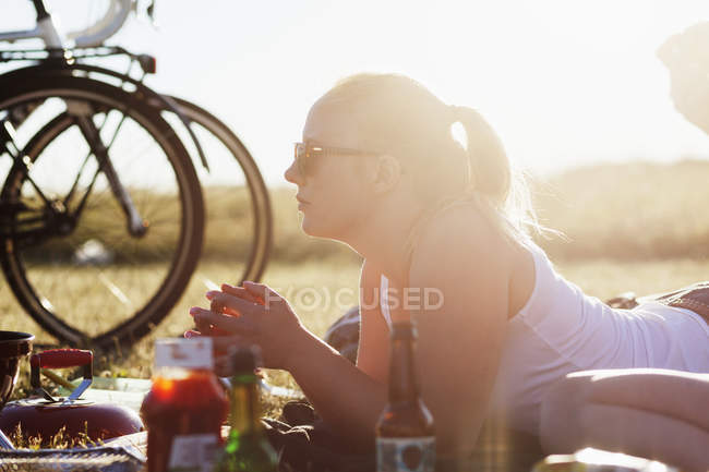 Woman lying with food and drink on field — Stock Photo