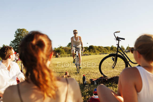 Man cycling while friends relaxing on field — Stock Photo