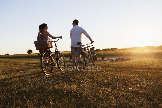Friends walking with bicycles on field — Stock Photo