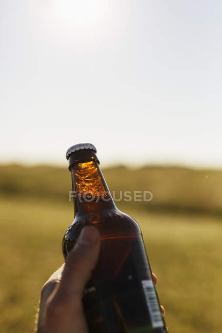 Homem segurando garrafa de cerveja — Fotografia de Stock