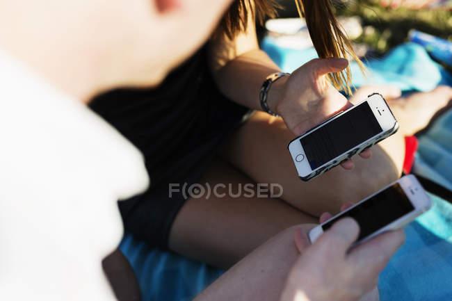Amigos usando telefones móveis em campo — Fotografia de Stock