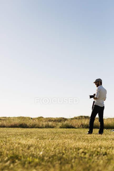 Uomo che tiene la fotocamera e in piedi sul campo — Foto stock