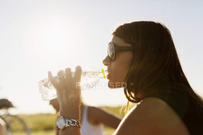 Woman drinking water from bottle — Stock Photo