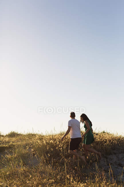 Coppia passeggiando sul campo erboso — Foto stock