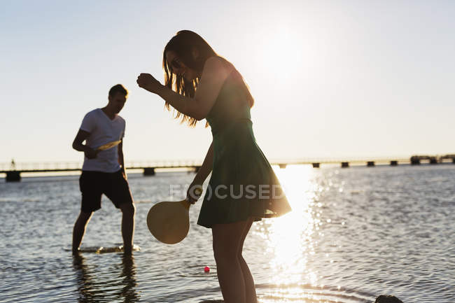 Couple playing tennis at shore — Stock Photo