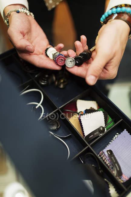 Fashion designer choosing buttons — Stock Photo