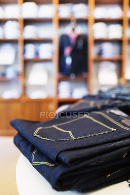 Folded jeans on table — Stock Photo