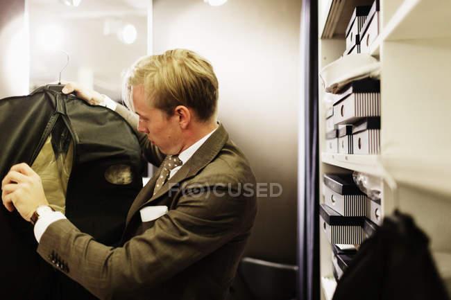 Sales clerk examining suit — Stock Photo