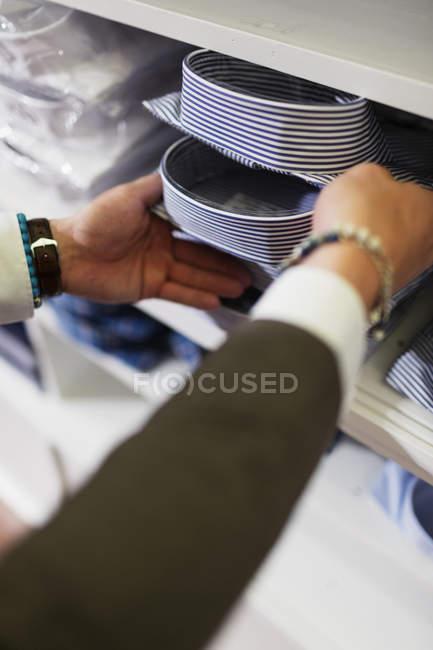 Sales clerk removing shirt from shelf — Stock Photo