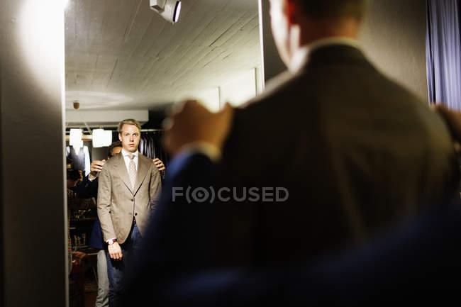 Sales clerk analyzing customers suit — Stock Photo