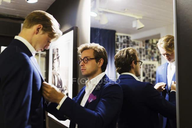 Продавец фитинг костюм на клиента — стоковое фото