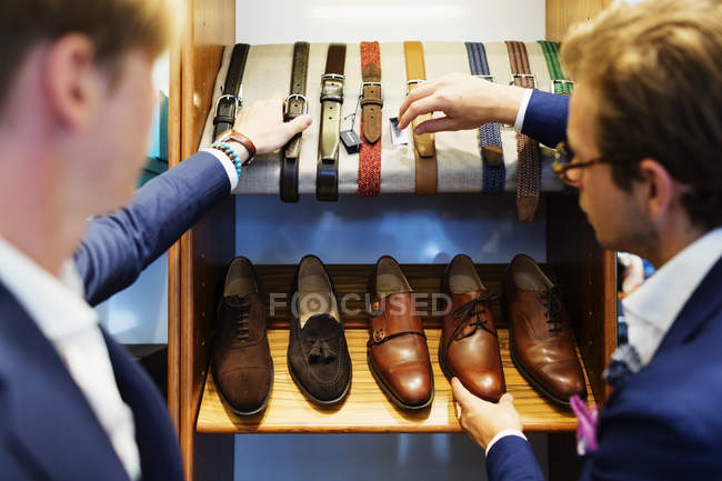 Salesman assisting customer in choosing belts — Stock Photo