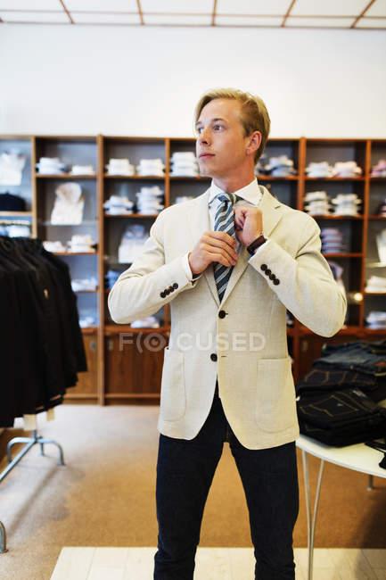 Handsome customer adjusting tie — Stock Photo