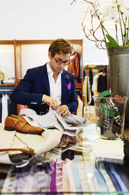 Sales clerk buttoning shirt — Stock Photo