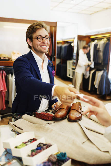 Cashier giving credit card to customer — Stock Photo