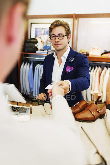 Customer giving credit card to cashier — Stock Photo