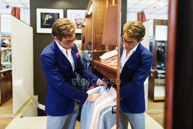 Salesman arranging suits — Stock Photo